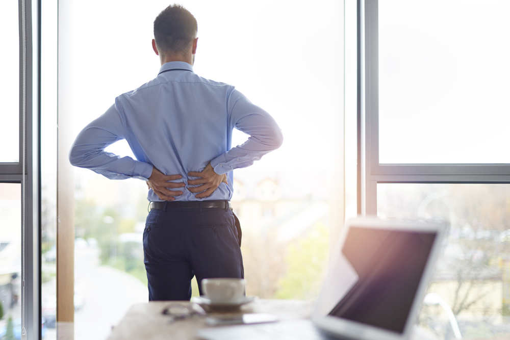 Man with lower back pain at work needs chiropractic care.
