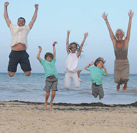 doctor limle's family on the beach jumping in the air